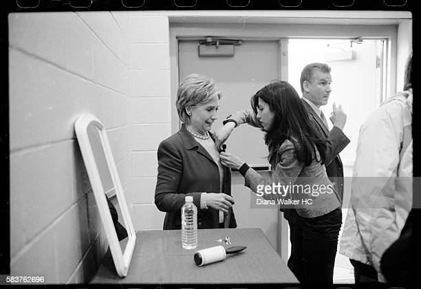 Presidential candidate Senator Hillary Rodham Clinton has a microphone attached to her lapel by her personal assistant Huma Abedin while waiting...