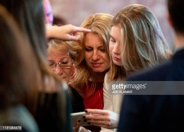 Presidential candidate Zuzana Caputova and her daughter Emma wait for the first exit polls with her friends at her election headquarters during the...