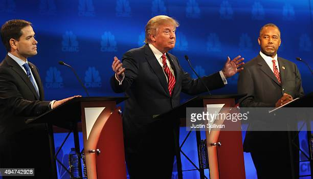 Presidential candidates Donald Trump speaks while Ben Carson and Sen Marco Rubio look on during the CNBC Republican Presidential Debate at University...