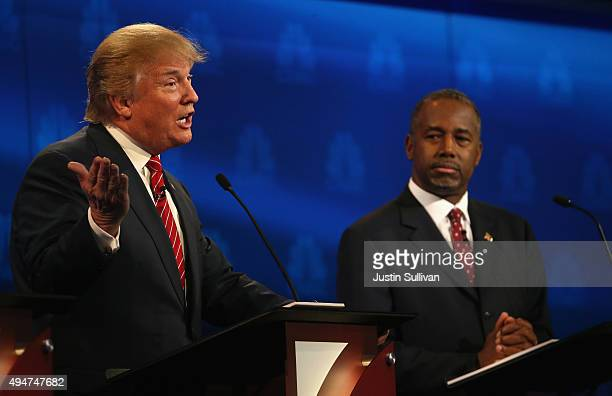 Presidential candidates Donald Trump speaks while Ben Carson looks on during the CNBC Republican Presidential Debate at University of Colorados Coors...