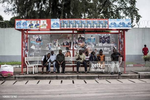 Presidential election posters stands above people waiting at a bus stop in Kinshasa Democratic Republic of the Congo on Friday Jan 11 2019 The...