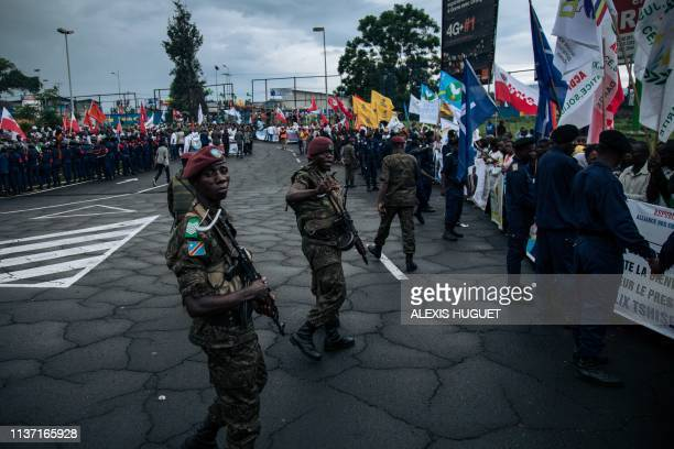 Presidential Guard and police forces link arms as they control the crowd before the arrival of the President Felix Tshisekedi at the airport of Goma,...