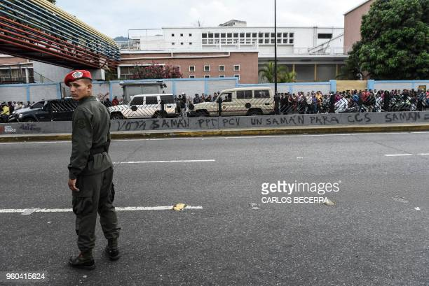 Presidential guard looks on as Venezuelans queue putside a polling station as they wait to cast their vote during the presidential elections in...