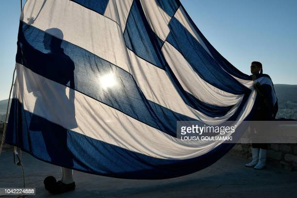TOPSHOT Presidential guards called Evzones hold the Greek flag during ceremony atop the Acropolis archaeological site in Athens on sunrise on...