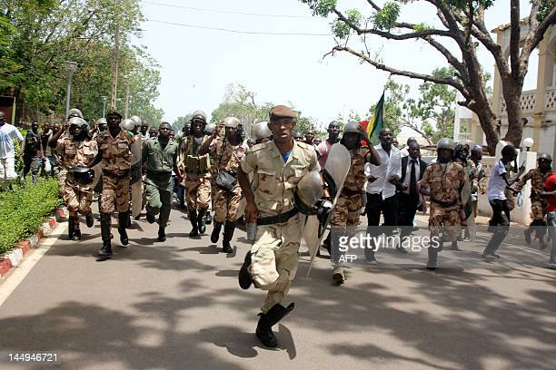 Presidential guards run to prevent some of thousands of Malians from storming on May 21 2012 the presidential compound in Bamako during a protest...