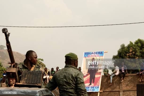 Presidential guards stand guard near a campaign poster of incumbent president during his opening campaign rally for the presidential election in...