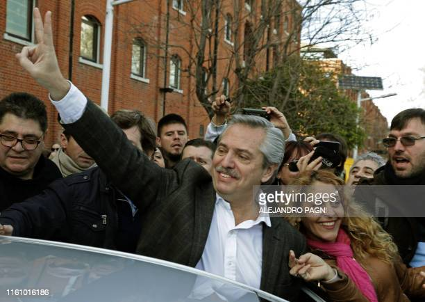Presidential hopeful for the Frente de Todos party Alberto Fernandez flashes the V sign after voting during primary elections in Buenos Aires on...