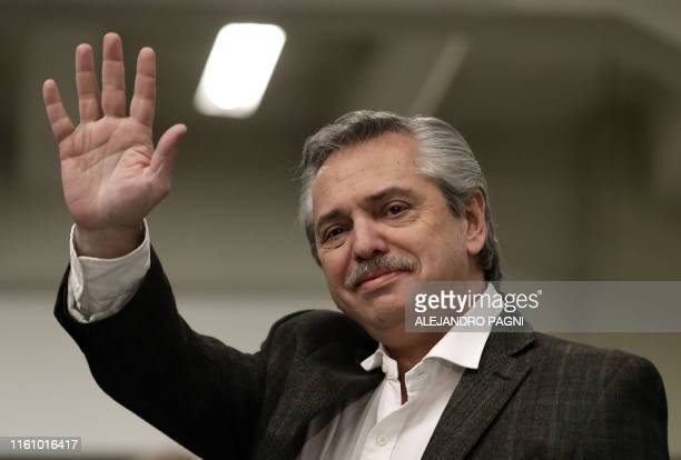 Presidential hopeful for the Frente de Todos party Alberto Fernandez waves before voting during primary elections in Buenos Aires on August 11 2019...