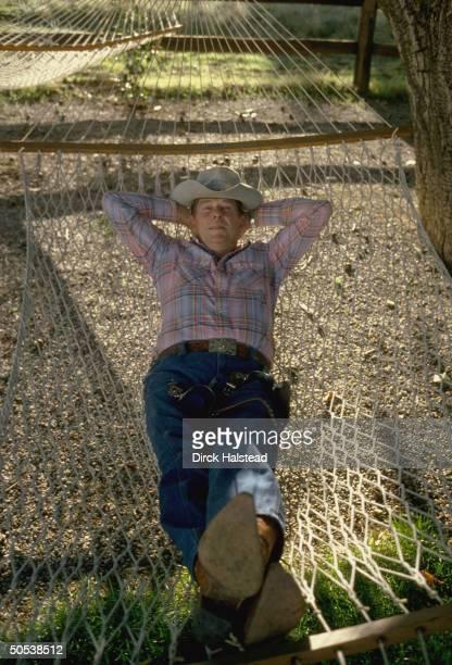Presidential hopeful Ronald Reagan relaxing in hammock outside