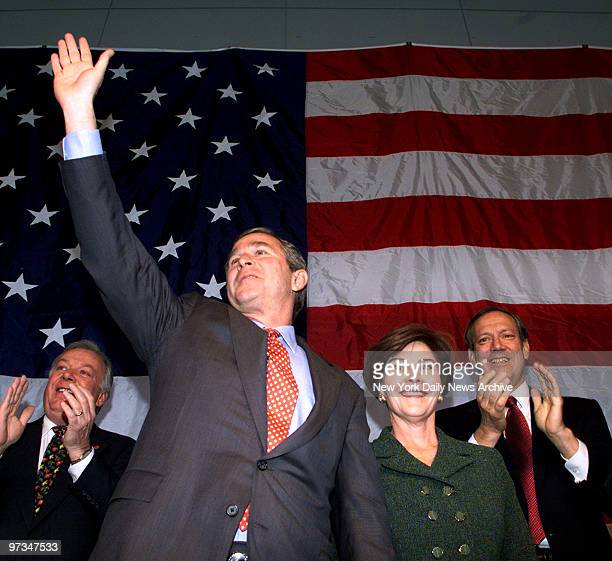 Presidential hopeful Texas Gov George W Bush waves during an airport campaign stop in New York State To his left are wife Laura and New York Gov...
