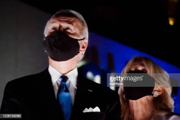 Presidential nominee and former US Vice President Joe Biden and wife Jill Biden wear face masks to watch a fireworks display during the closing...