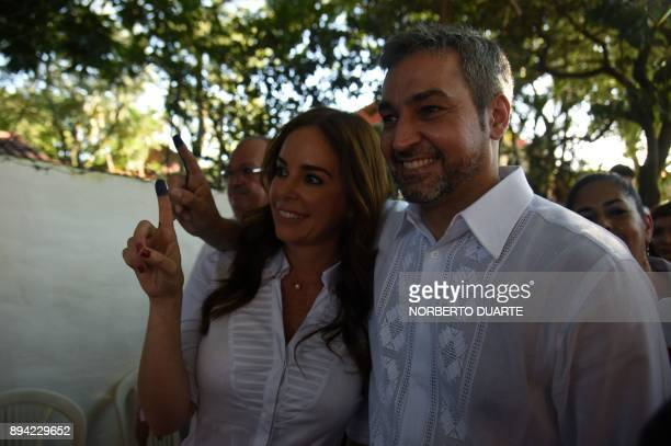 Presidential precandidate Mario Abdo Benitez and his wife Silvana Lopez Moreira show their inked finger after voting during Paraguay's rightwing...