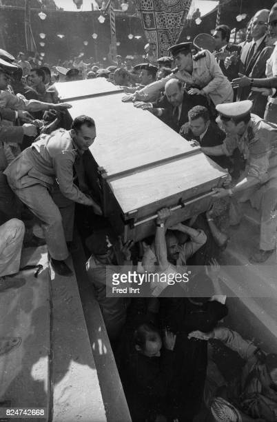 Presidents Gamal Abd al-Nasser coffin getting lifted into it´s final place. Crowds are in the way. Soldiers help to hold back the crowd. People are...