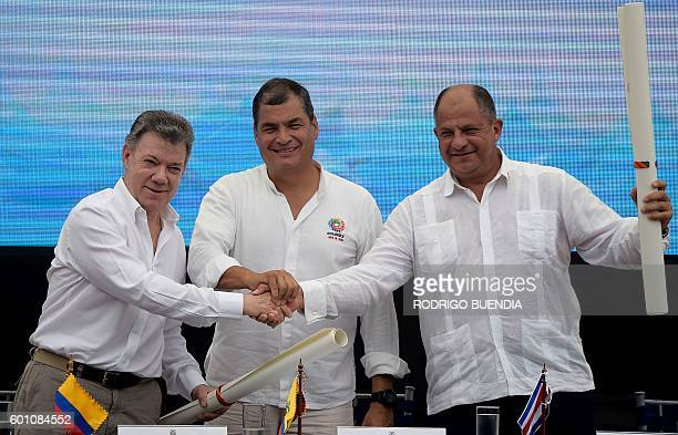 Presidents Juan Manuel Santos of Colombia Rafael Correa of Ecuador and Luis Guillermo Solis of Costa Rica pose for pictures after signing an...