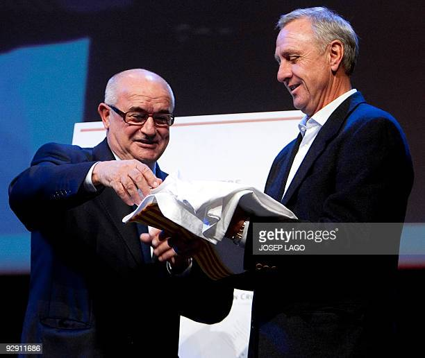President's of the Catalonia Football Federation Jordi Casals presents a gift to former Holland and Barcelona football star Johan Cruyff during a...