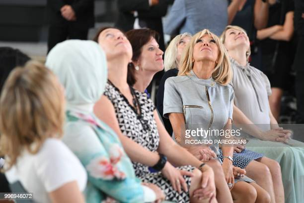 President's wife Brigitte Macron looks towards the ceiling next to Estonian Prime Minister's wife Karin Ratas Belgian Prime Minister's partner Amelie...