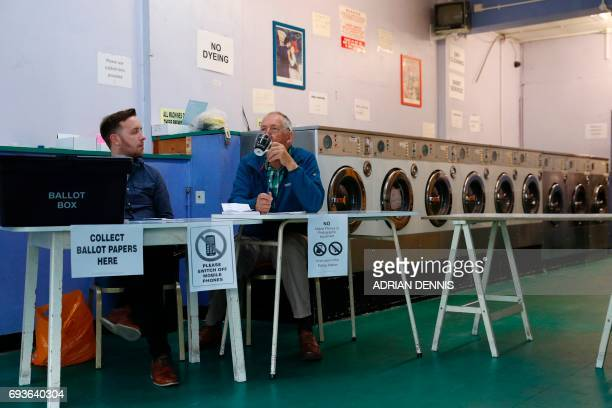 A presiding officer and poll clerk wait for early morning voters at a Polling Station set up in a launderette in Headington outside Oxford west of...