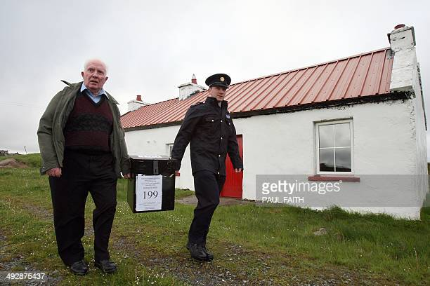 Presiding officer Hugh O'Donnell and Garda officer PJ McHugh arrive on the Island of Inishfree off the northwest coast of Ireland with a ballot box...