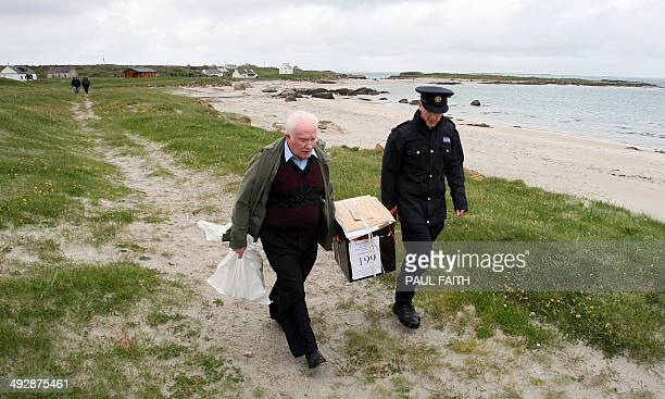 Presiding officer Hugh O'Donnell and Garda officer PJ McHugh leave the Island of Innishfree off the northwest coast of Ireland on May 22 with the...