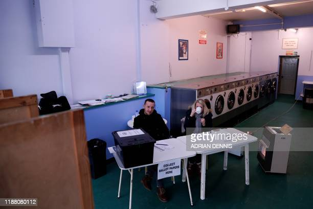 Presiding Officer Ian Williams and Polling Clerk Amelia Ball sit by portable heaters as they wait for voters to arrive inside a laundrette set up as...