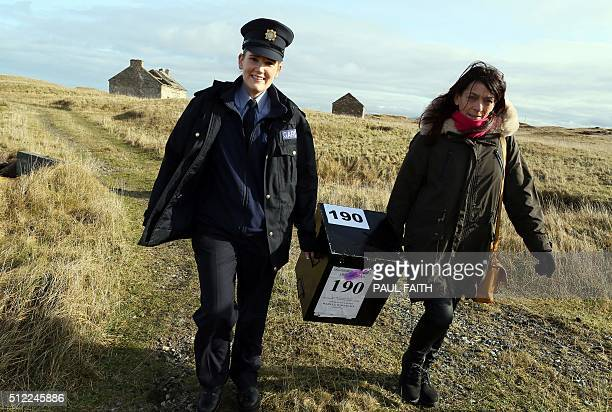 Presiding officer Majella Harkin and police officer Margaret Byrne arrive on the island of Inishfree off the west coast of Ireland on February 25...