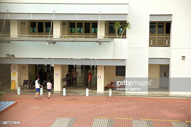 Presiding officers wait to check the citizens' polling cards and identity cards outside one of the polling stations during the Singapore General...