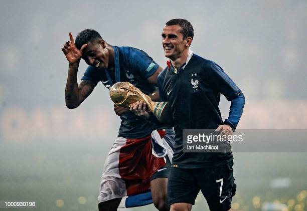 Presnel Kimpembe and Antoine Griezmann of France are seen with the trophy during the 2018 FIFA World Cup Russia Final between France and Croatia at...