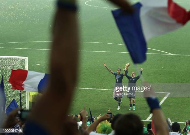 Presnel Kimpembe and Antoine Griezmann of France of France celebrate victory following the 2018 FIFA World Cup Final between France and Croatia at...