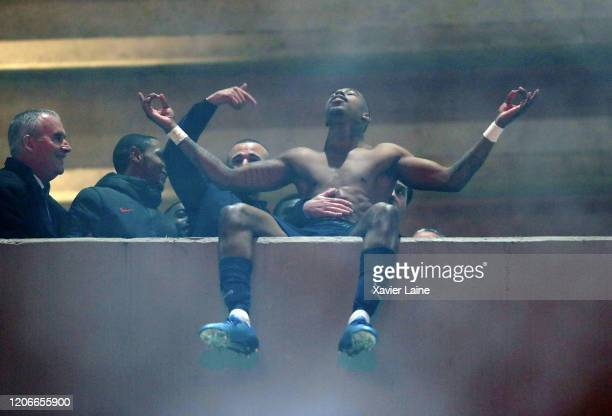 Presnel Kimpemebe of Paris SaintGermain and teammattes celebrate the victory with fans outside the stadium after UEFA Champions League round of 16...