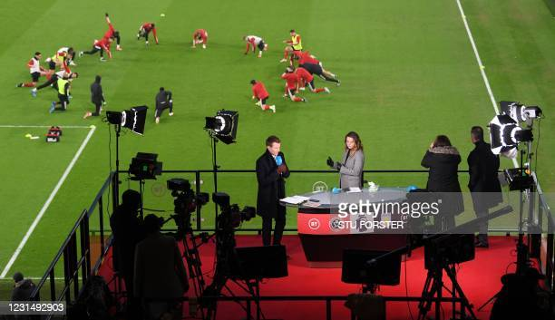 Presrenters for BT Sport work in their media booth as players warm up ahead of the English Premier League football match between Sheffield United and...