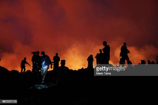 Press and onlookers stand on newly hardened lava to catch a view as lava erupts and flows from a Kilauea volcano fissure in the vicinity of Leilani...