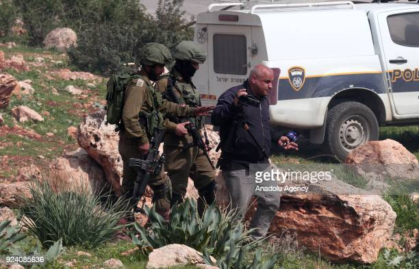 A press member is escorted by Israeli soldiers as they intervene in a protest by Palestinians against Jewish settlers seizing lands in the area near...