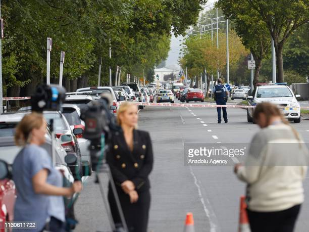 Press members wait around the scene as police officers cordon off the area after gunmen attacked the two mosques and fired multiple times during...