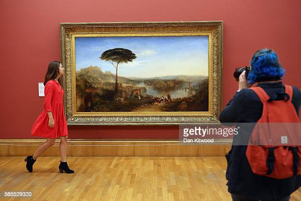 A press officer walks past a painting entitled 'Childe Harold's Pilgrimage' by Joseph Turner during a photocall at the Tate Britain on August 3 2016...
