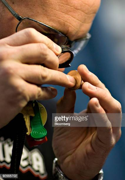 Press operator Chris Wright checks the edge lettering on new one dollar coin at the United States Mint in Denver Colorado US on Monday Oct 19 2009...