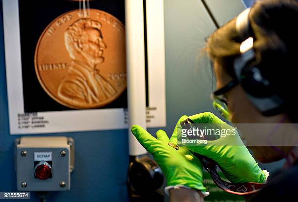 Press operator Siltham Smith inspects a freshly minted penny at the United States Mint in Denver Colorado US on Monday Oct 19 2009 The yen and dollar...