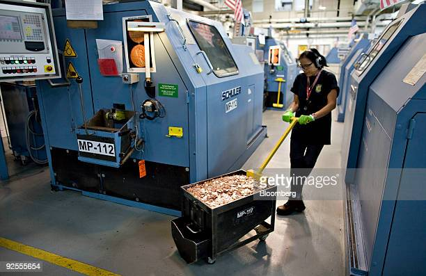 Press operator Siltham Smith moves a container of freshly minted pennies at the United States Mint in Denver Colorado US on Monday Oct 19 2009 The...
