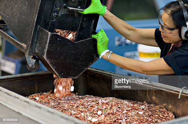 Press operator Siltham Smith pours a load of freshly minted pennies into a container at the United States Mint in Denver Colorado US on Monday Oct 19...