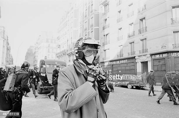 A press photographer and riot police during civil unrest in the streets around the Sorbonne Paris 12th June 1968 The photographer is wearing a...