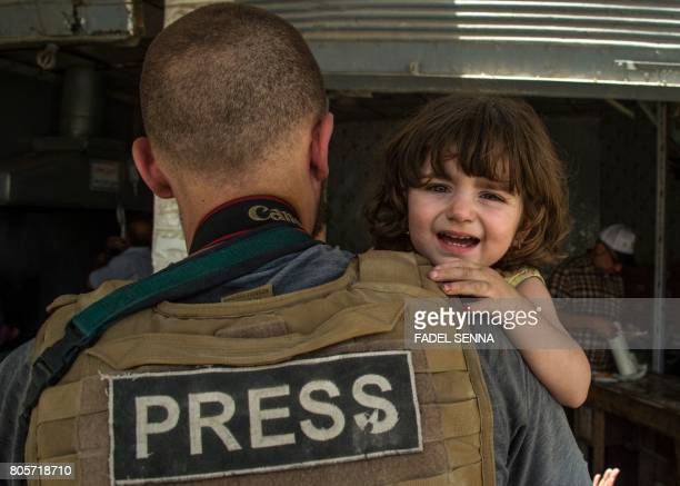 A press photographer helps carry a child who fled from the Old City of Mosul in the city's western industrial district on July 2 during the...