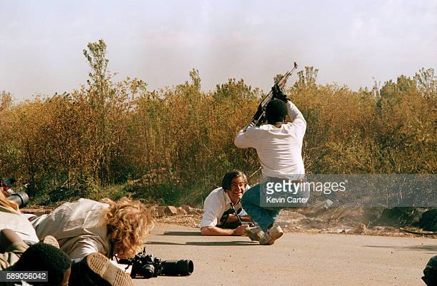 Press photographer James Nachtwey takes cover during a street battle between African National Congress supporters and Zulu miners loyal to the...