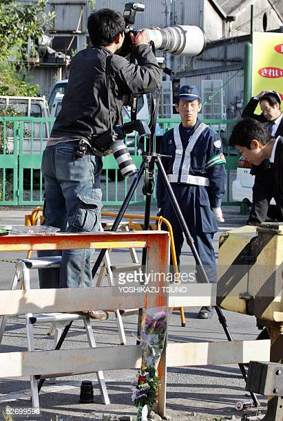 A press photographer takes pictures before a policeman standing guard while flower bouquets are placed near the train crashed site at Amagasaki city...