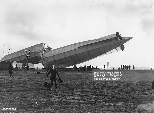 A press photographer walks away as Britain's first military airship HMA No 1 the 'Mayfly' lies broken in two in Cavendish Dock at the Vickers Sons...