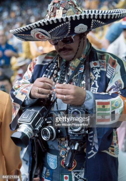 A press photographer wearing sunglasses and a sombrero with a collection of cameras and pins during the opening ceremony of the Summer Olympic Games...