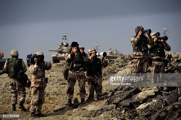 Press photographers and a television reporter dressed in military fatigues capture images of the Gulf War