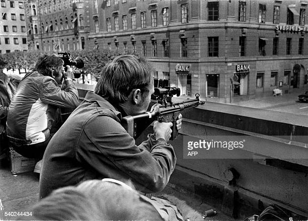 Press photographers and police snipers lie side by side on a roof opposite the Kreditbanken bank on Norrmalmstorg square in Stockholm 24 August 1973...