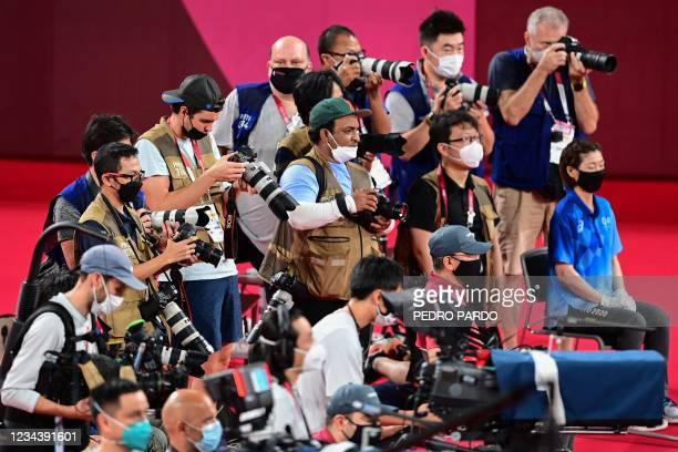 Press photographers capture the women's doubles badminton medals ceremony during the Tokyo 2020 Olympic Games at the Musashino Forest Sports Plaza in...
