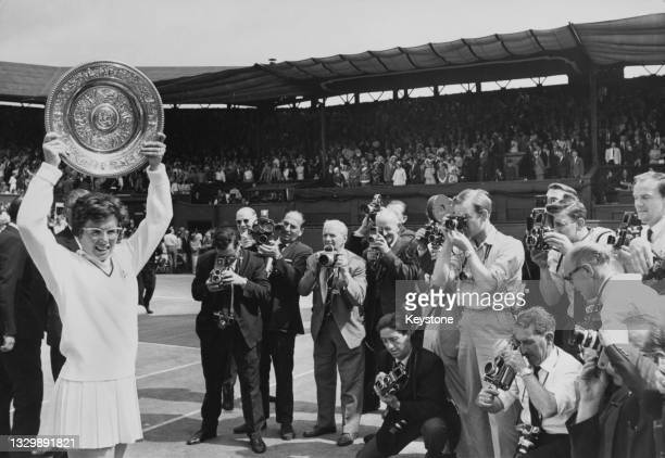 Press photographers gather around as Billie Jean King of the United States holds the Venus Rosewater Dish after defeating Maria Bueno of Brazil in...