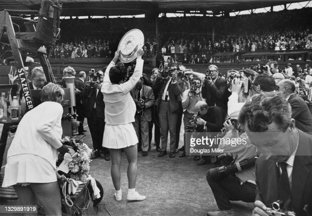Press photographers gather around as Billie Jean King of the United States holds the Venus Rosewater Dish aloft after defeating Ann Jones of Great...