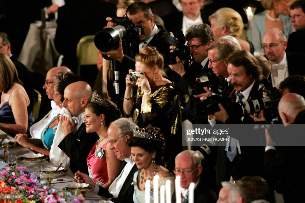 Press photographers gather behind the guests of honor, physics laureate David H. Politzer, Crown Princess Victoria, physics laureate David J. Gross and Queen Silvia at the Nobel Banquet in Stockholm City Hall, Stockholm, 10 December 2004.